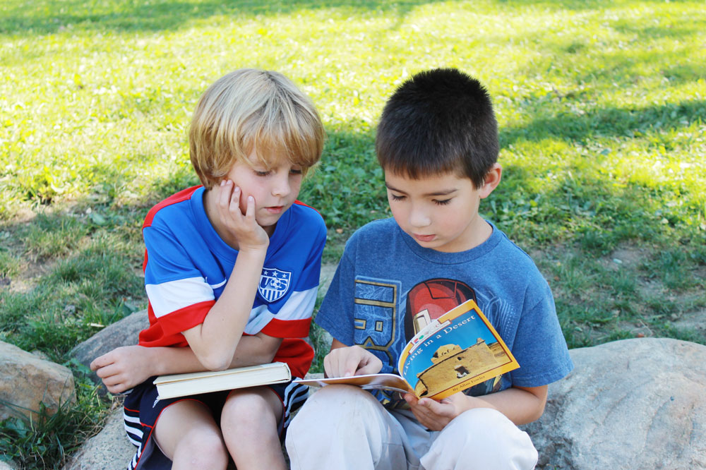 Montessori Elementary Students Reading a Book Outdoors
