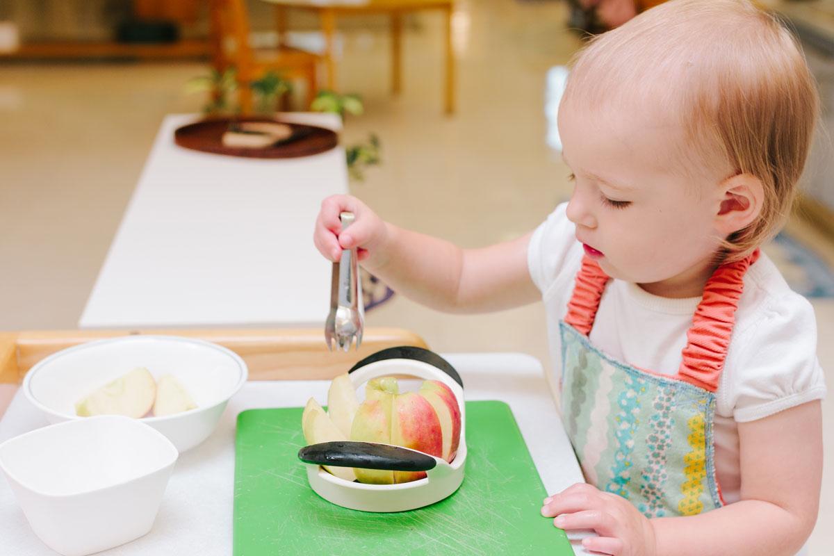 Montessori toddler slicing apples as food prep
