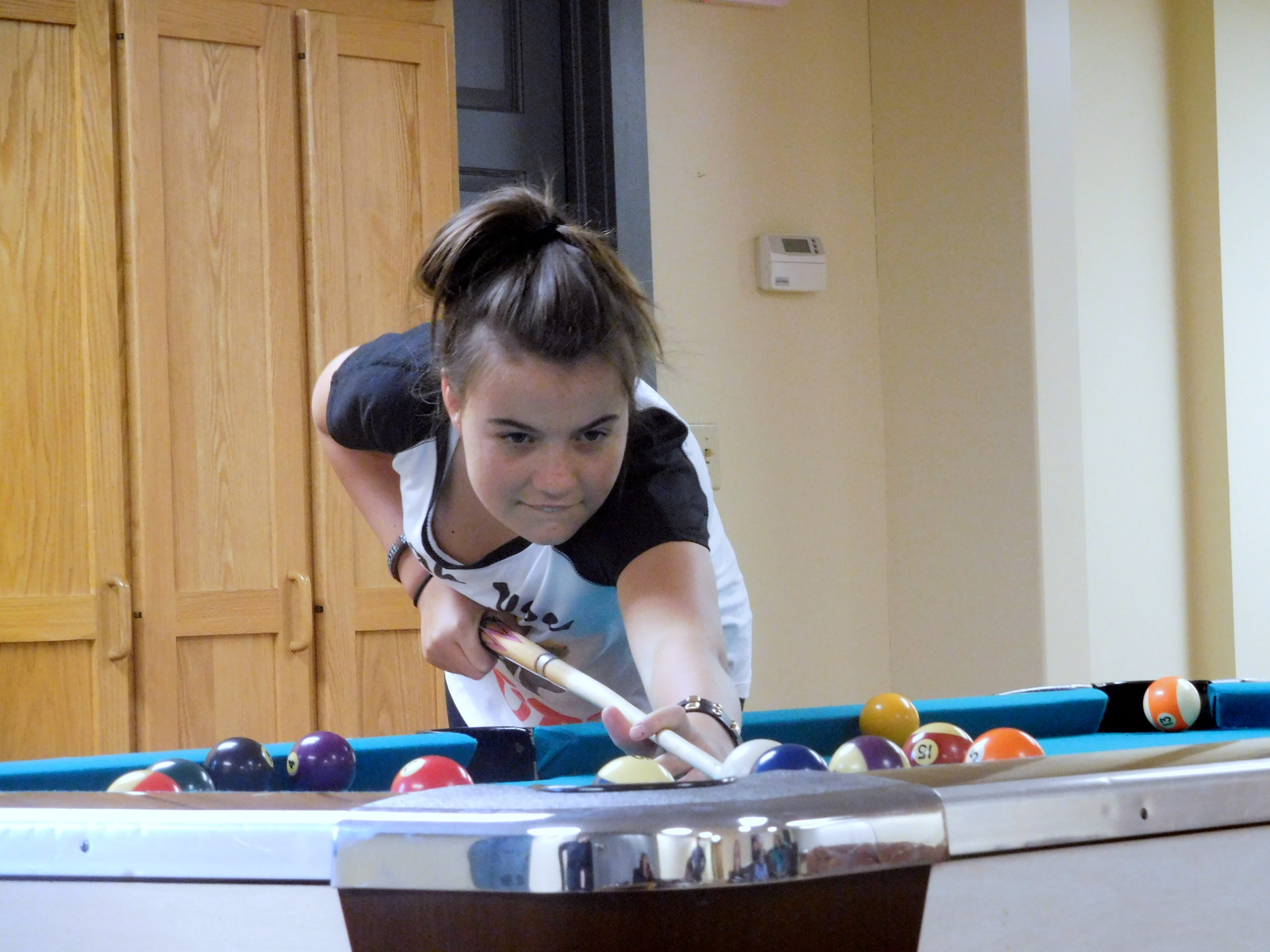 Montessori boarding student playing pool in her freetime